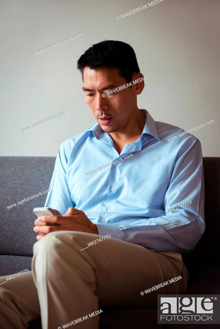 Stock Photo: Man using mobile phone in living room.