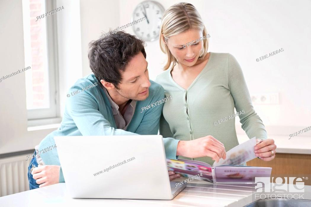 Stock Photo: Couple reading a book in front of a laptop.