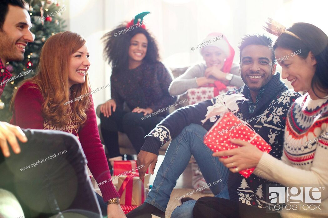 Stock Photo: Friends opening Christmas gifts in living room.