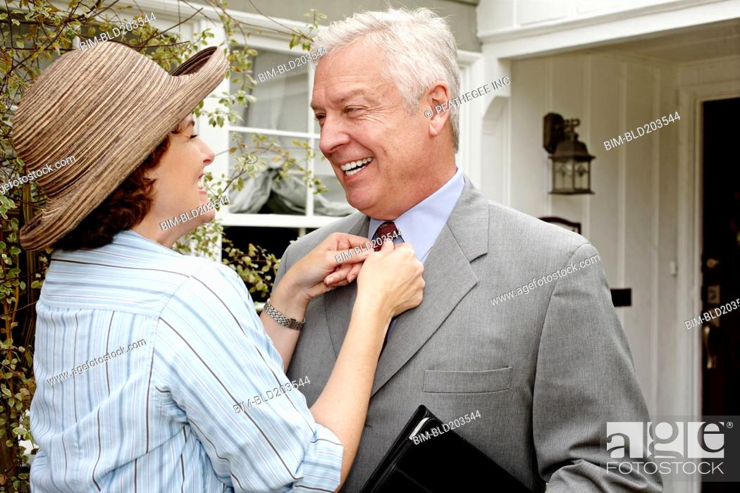 Photo de stock: Woman adjusting husband's tie on front path.