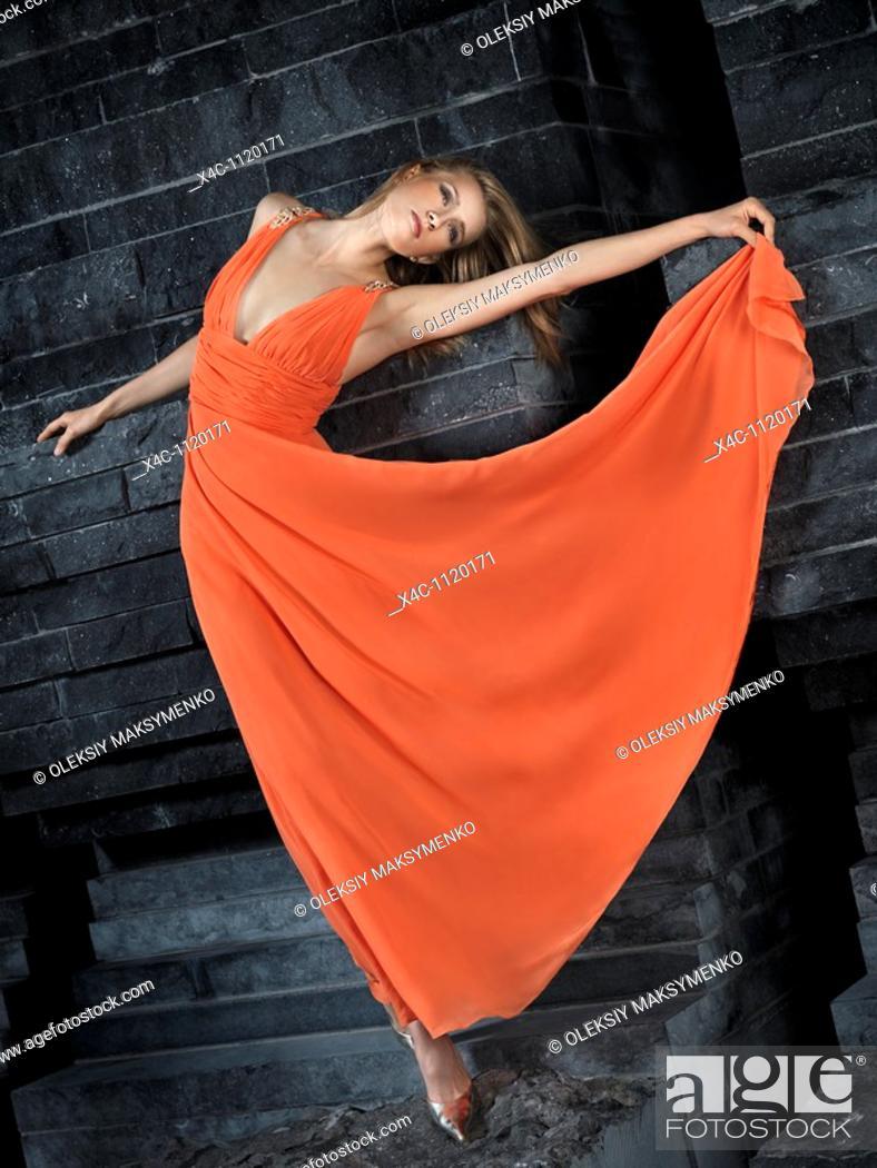 Stock Photo: Beautiful woman in long orange dress leaning against black granite wall.