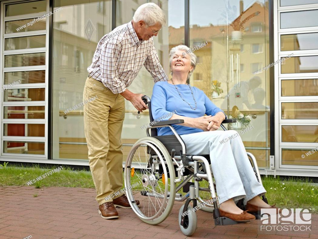 Stock Photo: Germany, Cologne, Senior man pushing woman in wheelchair.