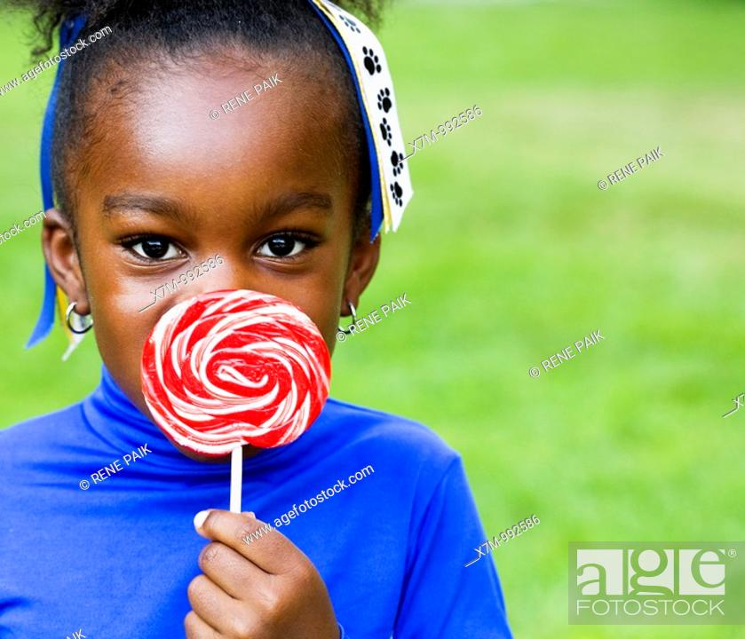 Stock Photo: A little black girl and her swirly lollipop.