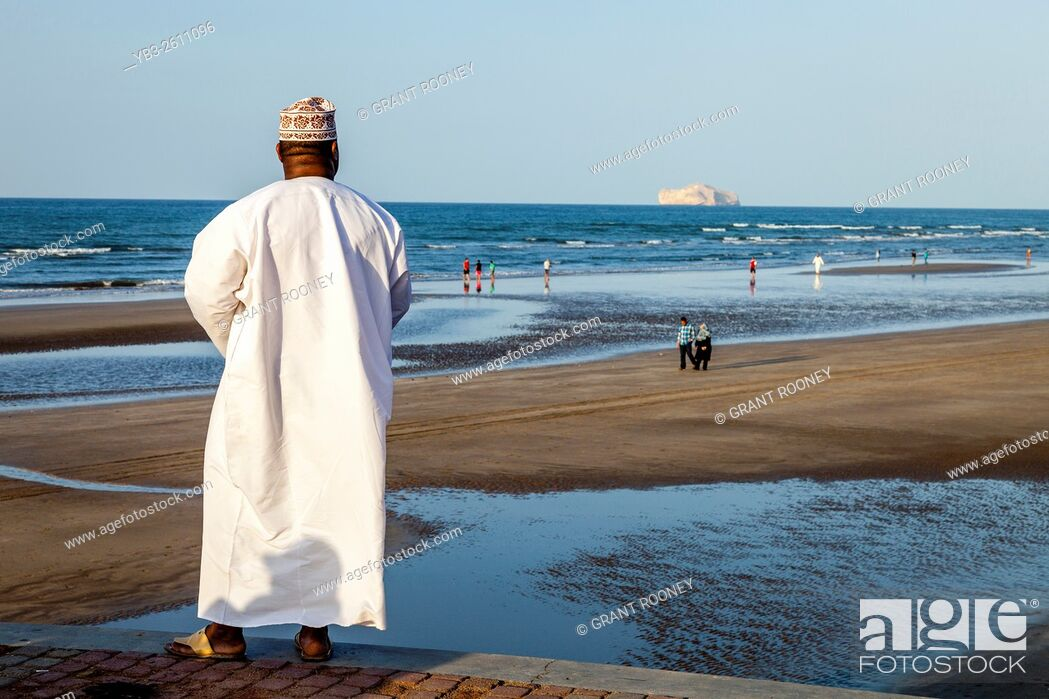 Stock Photo: An Omani Man In Traditional Dress Looks Out Over The Beach At Muscat, Sultanate Of Oman.