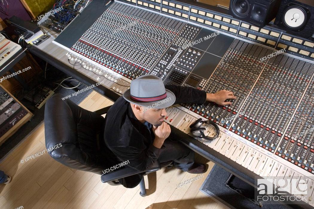 Stock Photo: Music producer adjusting sound equipment.