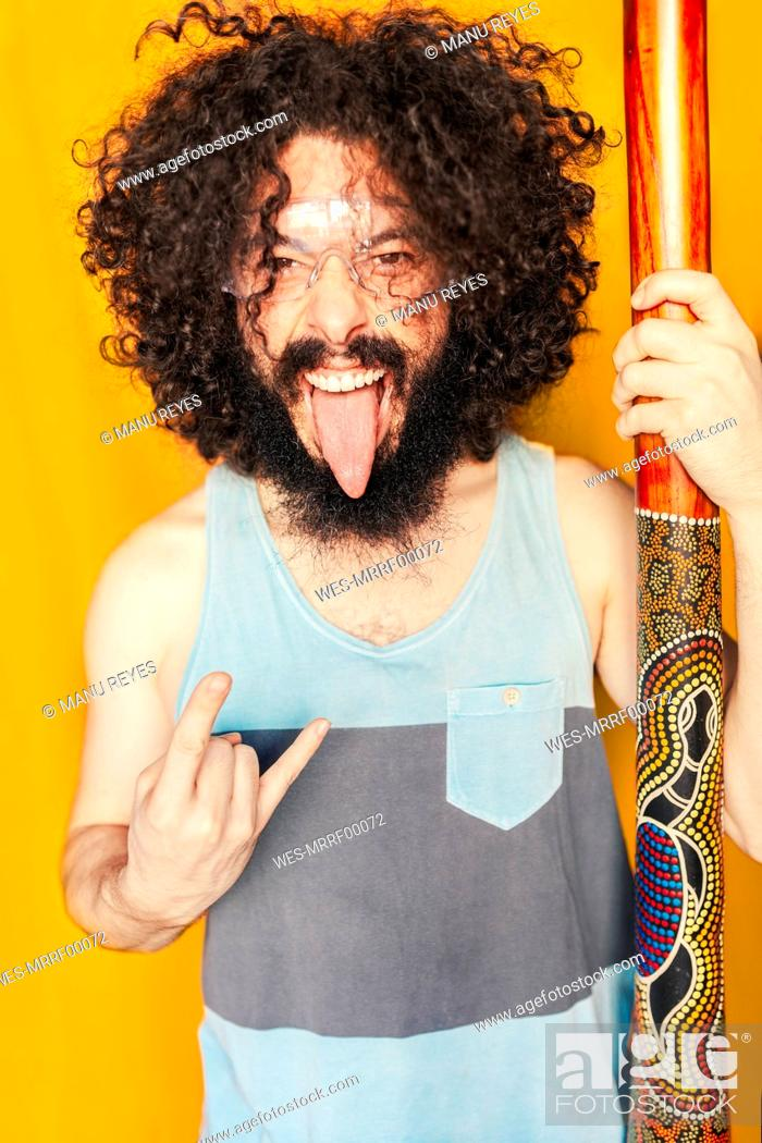 Stock Photo: Crazy man with curly hair holding didgeridoo while sticking out tongue against yellow background.