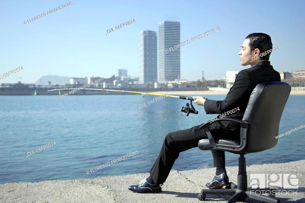 Stock Photo: Business man fishing by seafront.