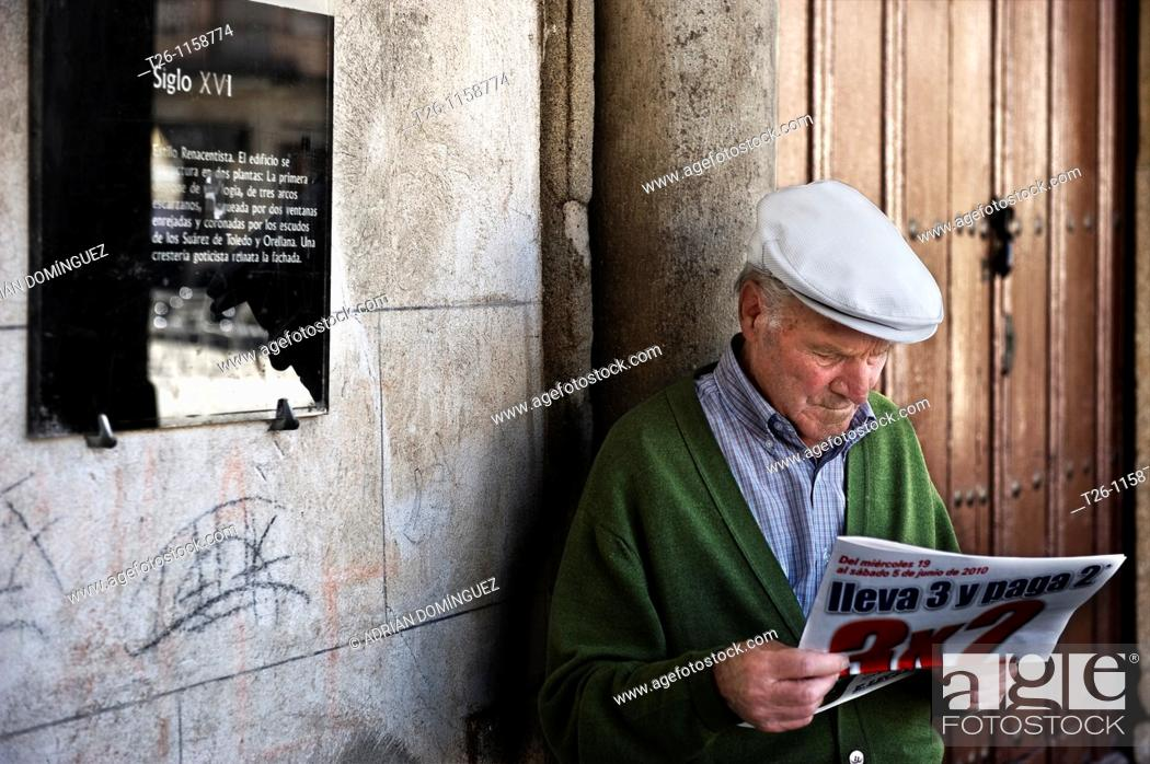 Stock Photo: Read local newspaper in the town square. Trujillo, Spain.