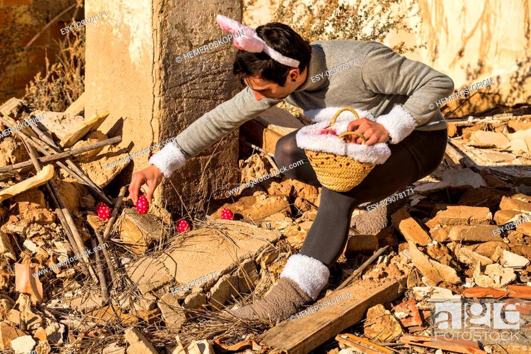 Stock Photo: Easter bunny hiding eggs among the rubble of an abandoned house.