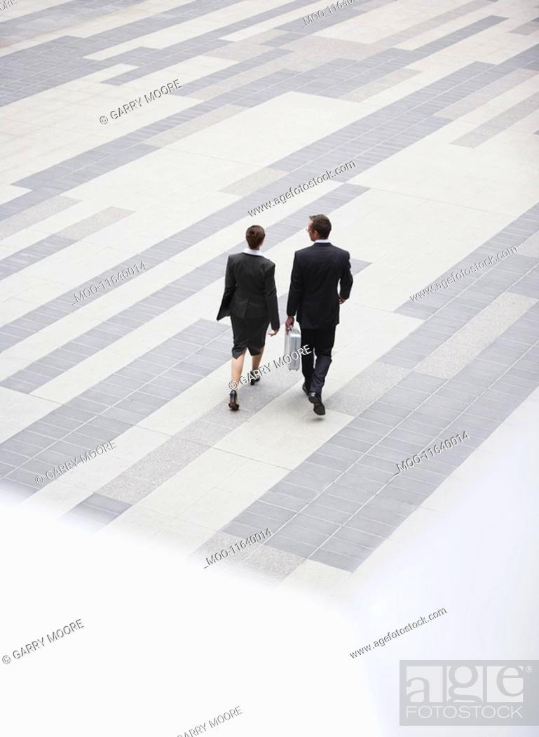 Stock Photo: Businessman and businesswoman walking across outdoor plaza elevated view back view.
