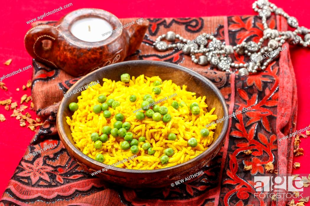 Imagen: Indian cuisine: bowl of yellow rice with green peas on red background.