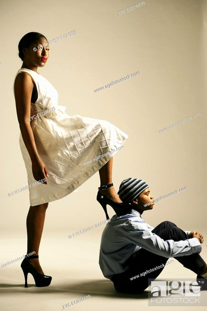 Stock Photo: Young African American woman stepping on man, studio shot.