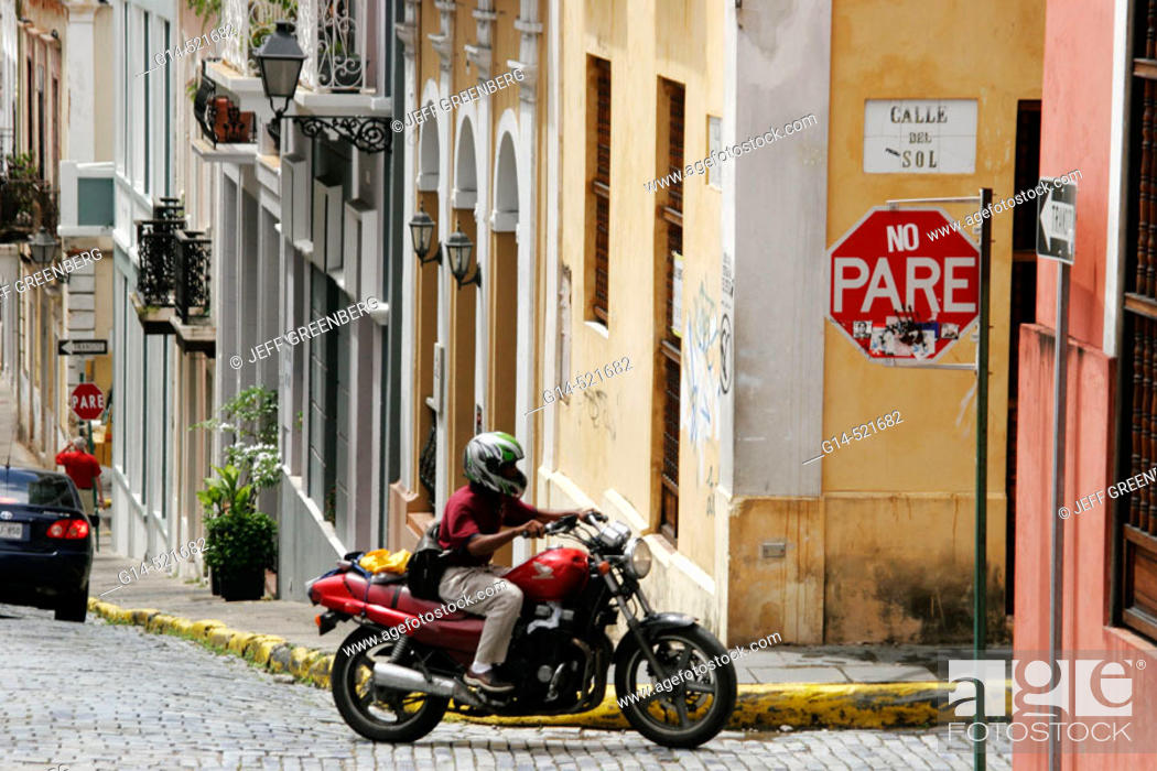 Stock Photo: Calle del Sol, architecture, steep hill, motorcycle, adoquine cobblestone, stop sign. Old San Juan. Puerto Rico.