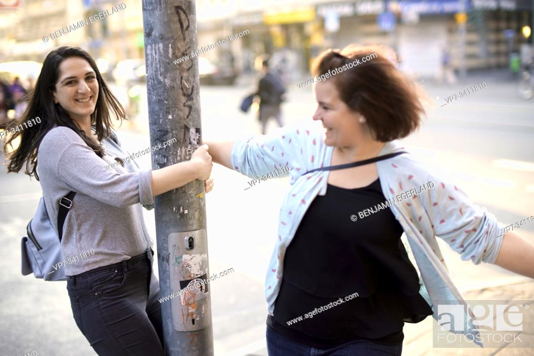 Stock Photo: two lively friends dancing around street lamp post in city.