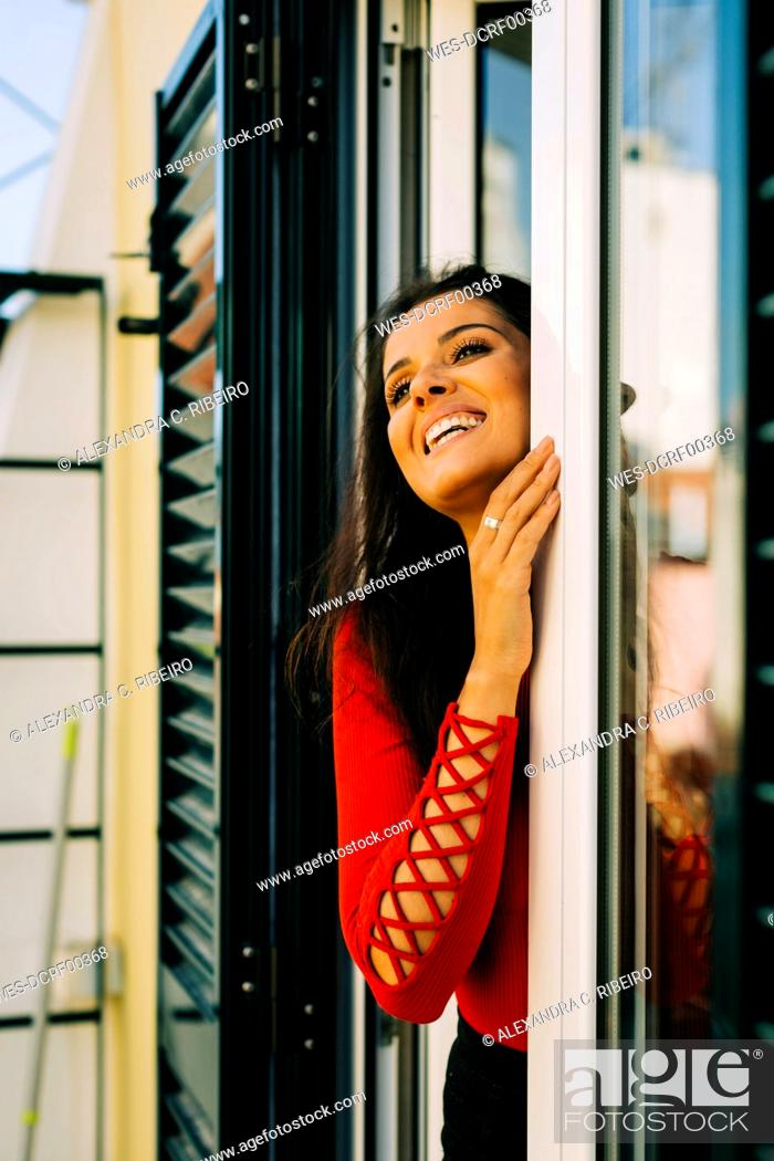 Stock Photo: Cheerful young woman looking away while standing by door at home.