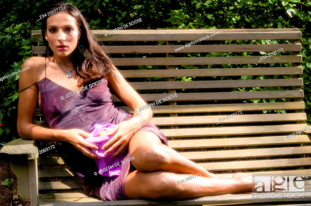Imagen: Portrait of a 27 year old brunette woman in a summer dress sitting on a bench looking at the camera in an outdoor setting holding a bowl of grapes.
