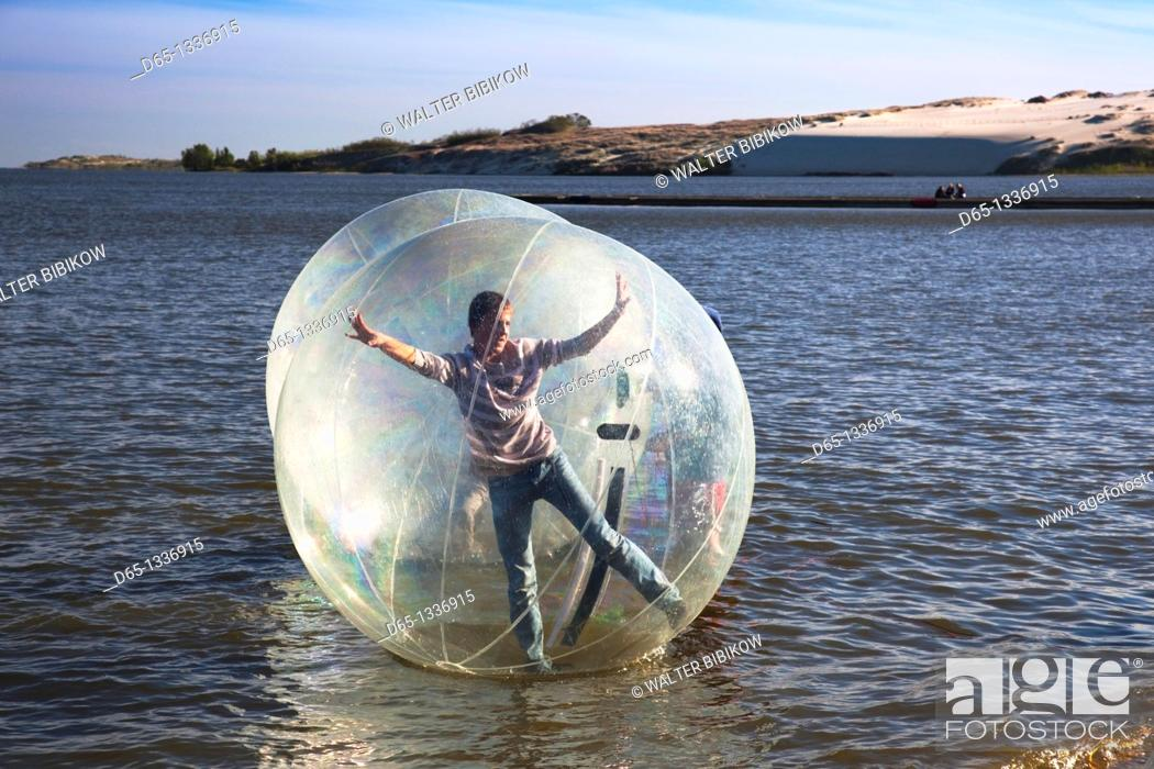 Stock Photo: Lithuania, Western Lithuania, Curonian Spit, Nida, kids in waterball, NR.