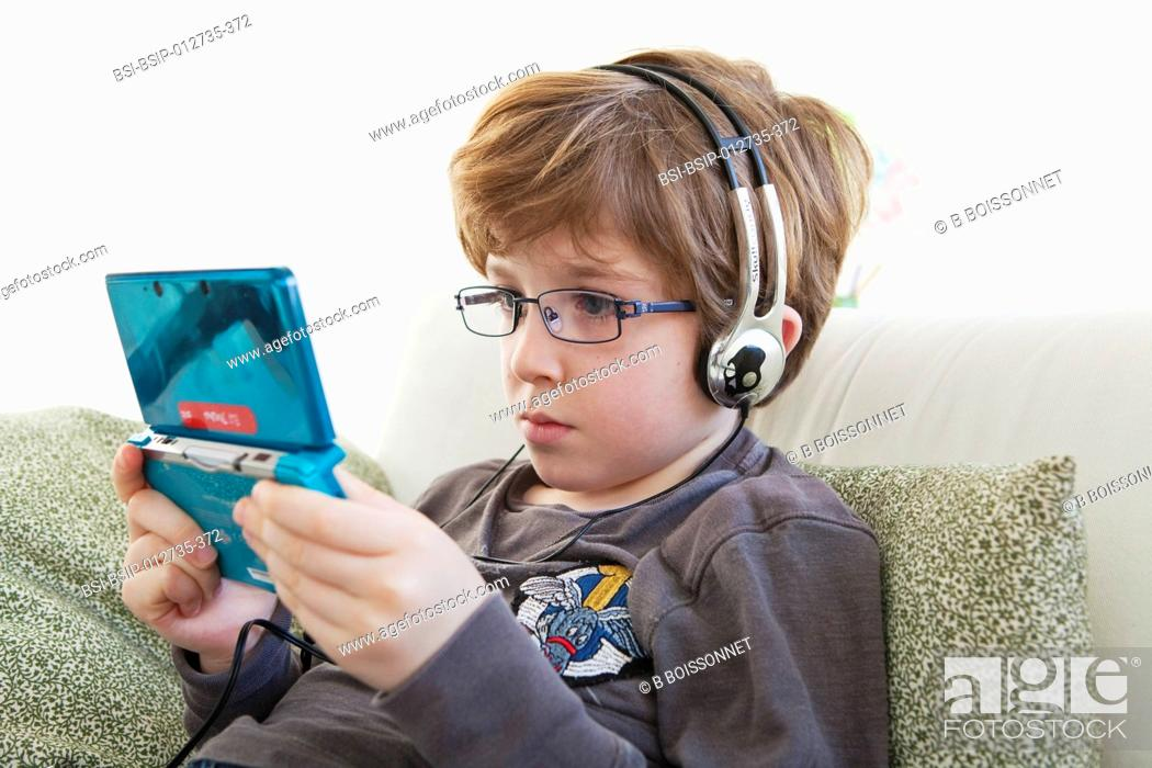 Stock Photo: CHILD PLAYING WITH VIDEO GAME.