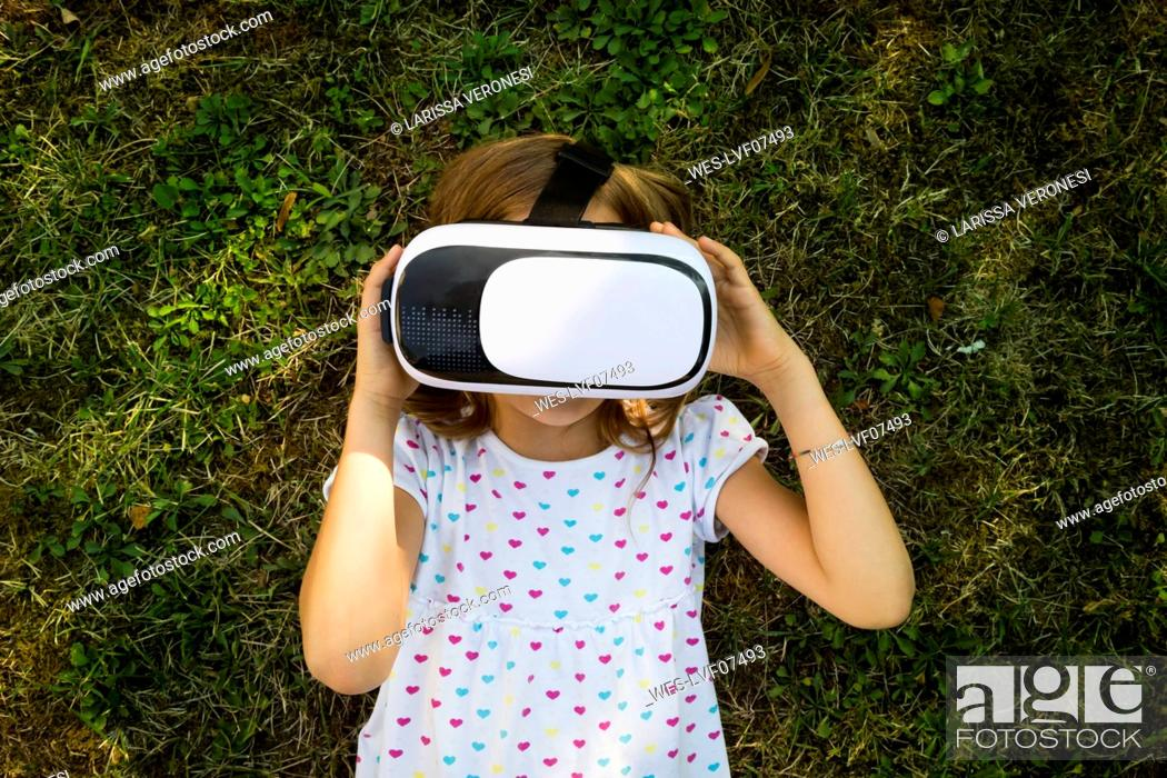 Stock Photo: Little girl wearing Virtual Reality Glasses lying on meadow in the garden.