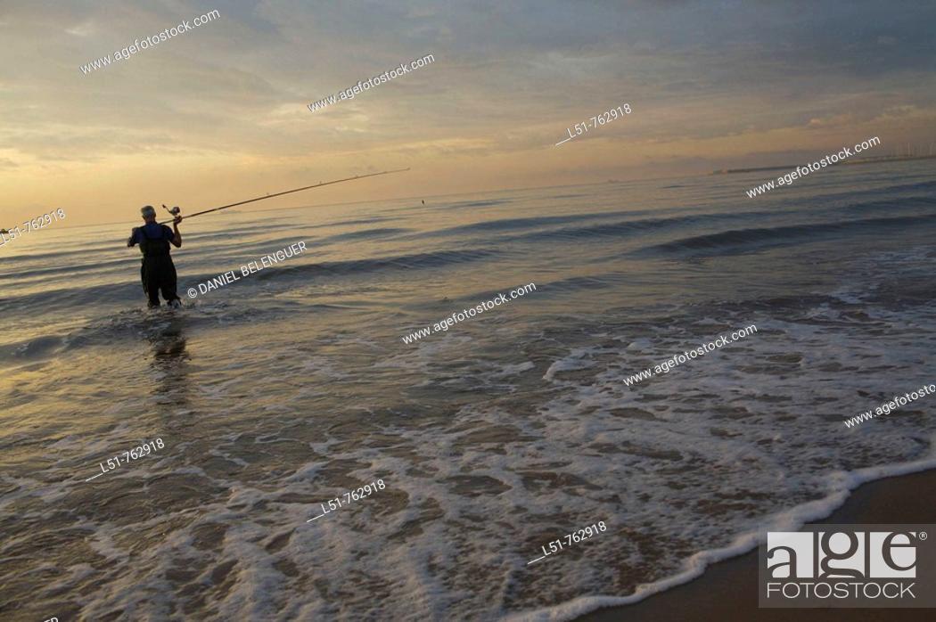 Stock Photo: Man fishing at sunrise on Malvarrosa beach, Valencia city, Valencia, Comunidad Valenciana, Spain, Europe.