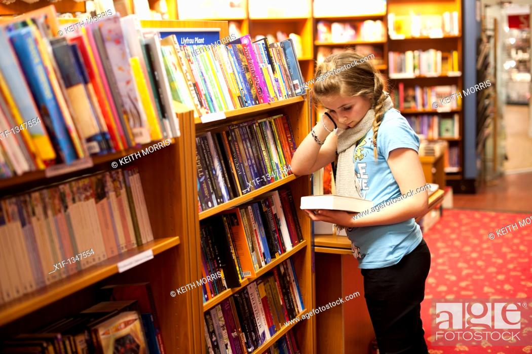 Stock Photo: A twelve year old teenage girl reading in a bookshop, UK.