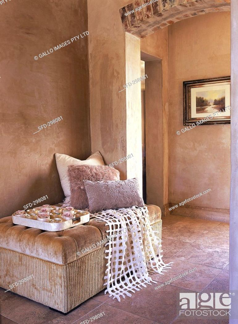 Stock Photo: Seating area with upholstered stool, cushions, throw and tray.