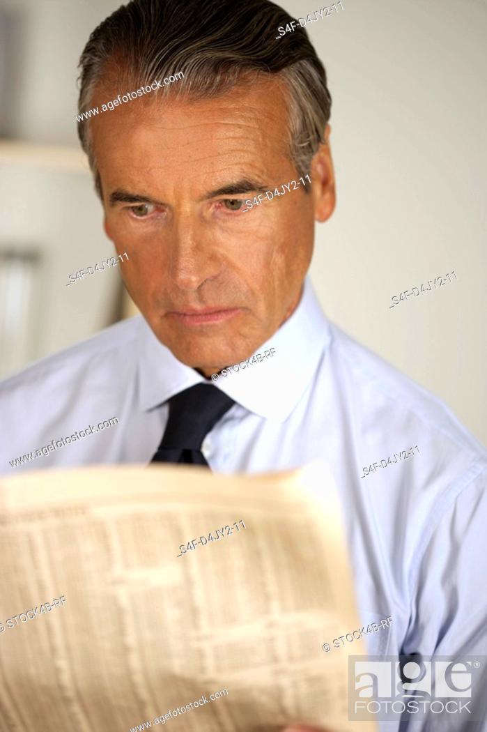 Stock Photo: Senior businessman reading a newspaper.