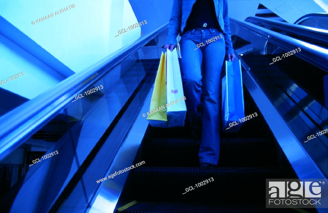 Stock Photo: Woman with shopping bags using escalator.