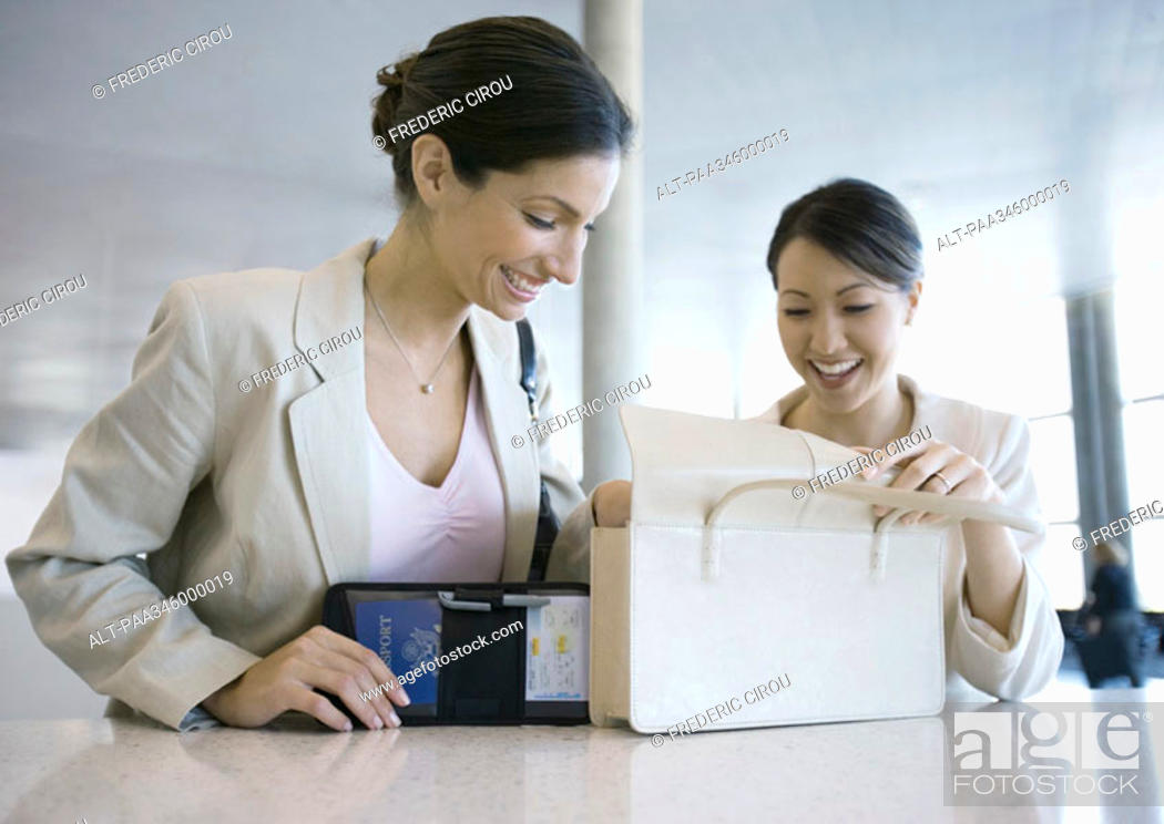 Stock Photo: Two women looking through purse together.