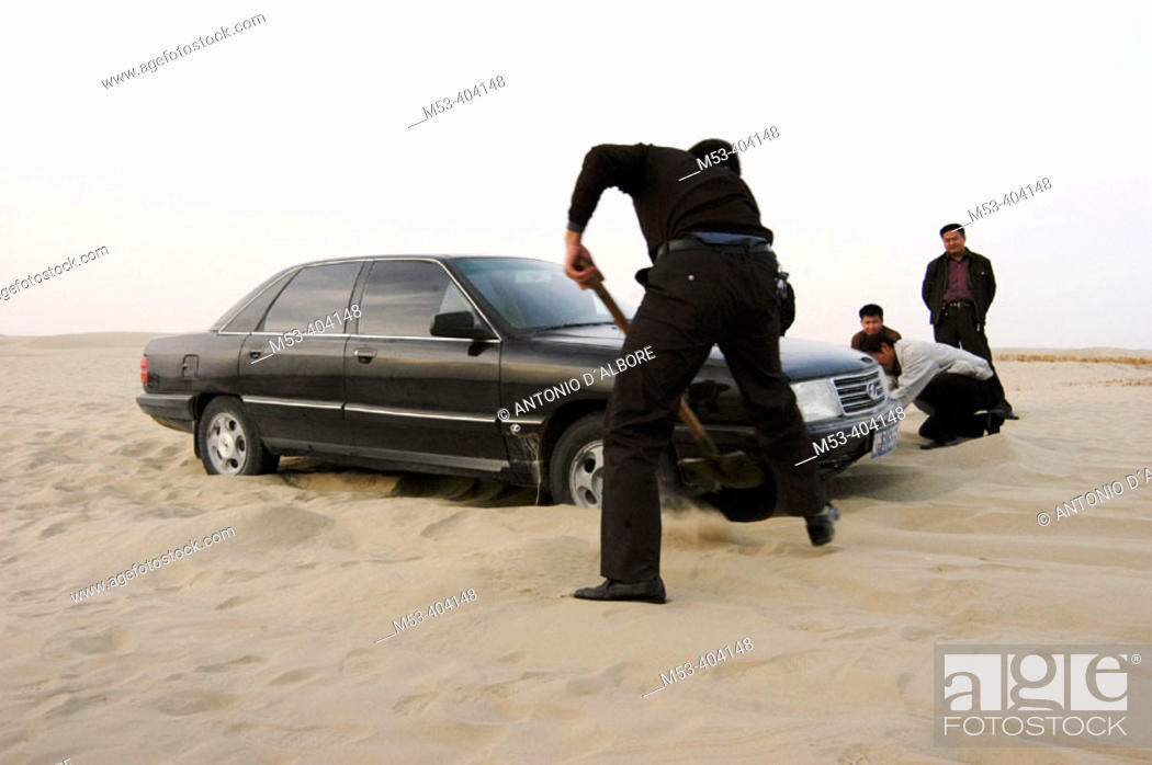 Stock Photo: Man remove sand from the bottom of a shelved car. Taklamakan desert. Xinjiang Uyghur Autonomous Region. China.