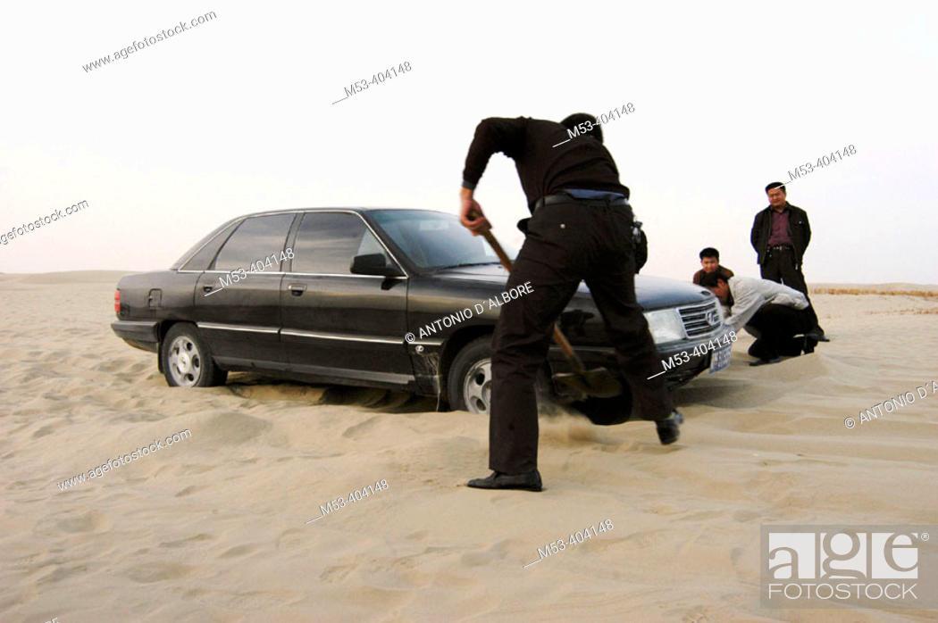 Stock Photo: Man remove sand from the bottom of a shelved car. Taklamakan desert. Xinjiang Uyghur Autonomous Region. China.