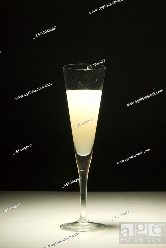 Stock Photo: An elegant glass of grapefruit juice on a black background.