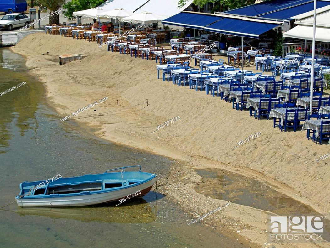 Stock Photo: empty blue tables of an open air restaurant on beach in Greece . - 24/05/2006.