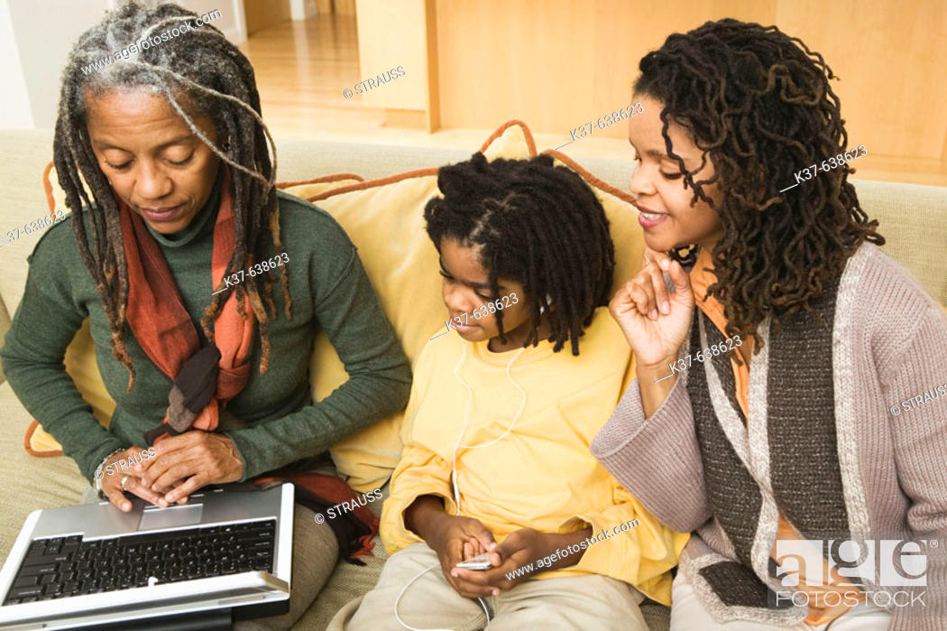 Stock Photo: 3 generations of African American family at home, with grandma using laptop being advised by older daughter & her grandson listening to his ipod.