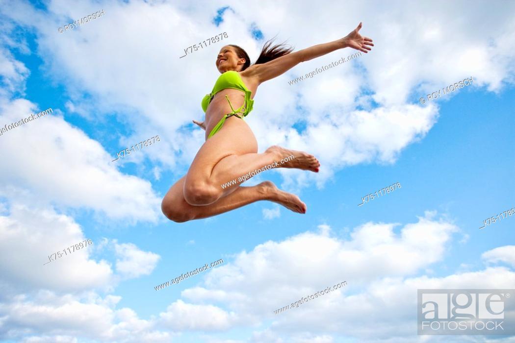 Stock Photo: Woman in bikini, jumping.