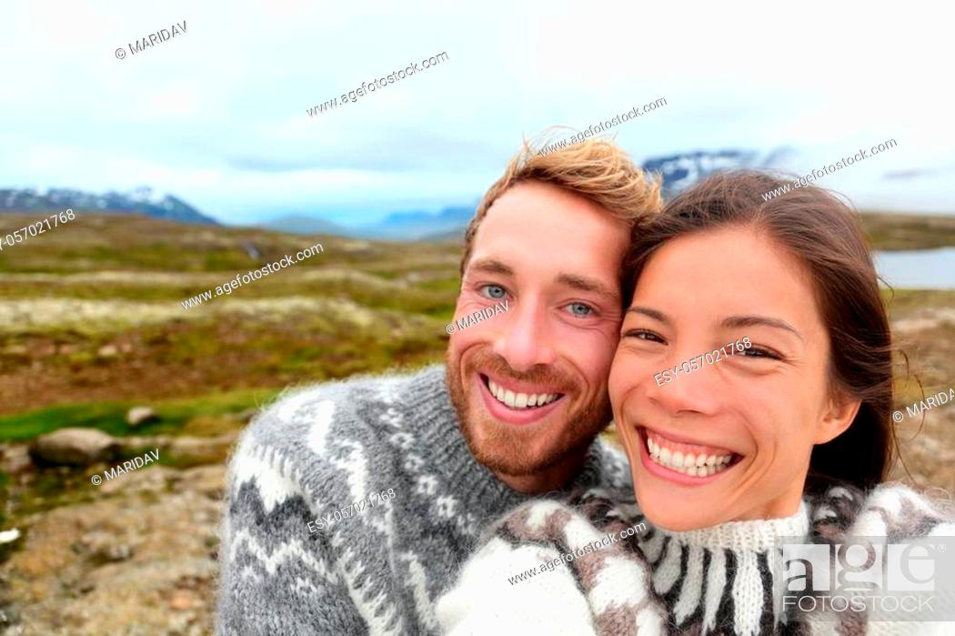 Stock Photo: Iceland couple selfie wearing Icelandic sweaters in beautiful nature landscape on Iceland. Woman and man model in typical Icelandic sweater.