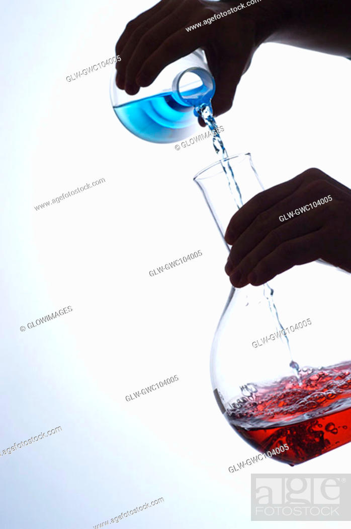 Stock Photo: Close-up of a person pouring liquid into a beaker.