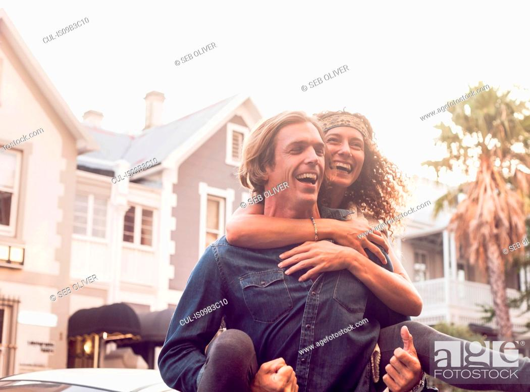 Stock Photo: Man giving girlfriend piggyback on street, Cape Town, South Africa.