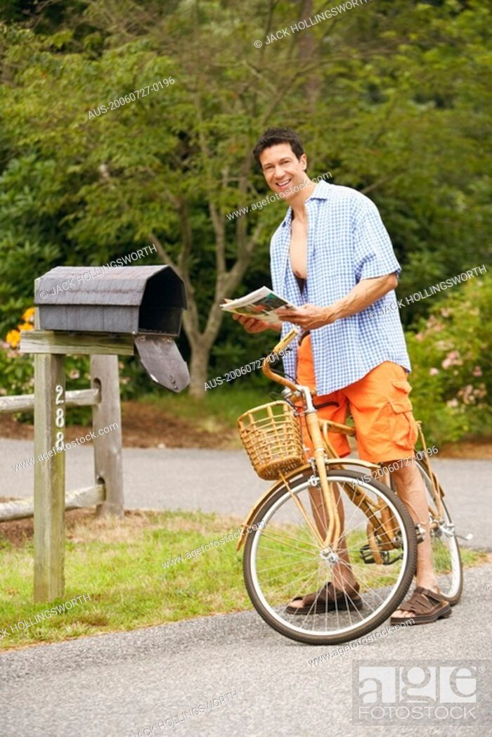 Stock Photo: Portrait of a mature man standing with a bicycle near a mailbox.