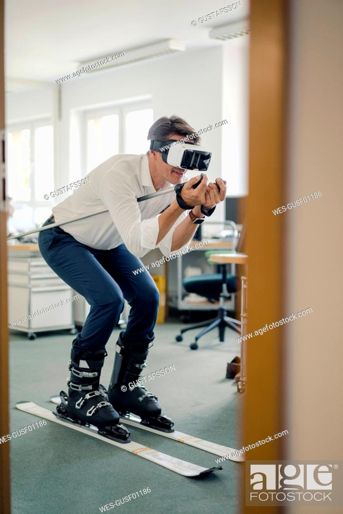 Photo de stock: Businessman skiing in office, using VR glasses.