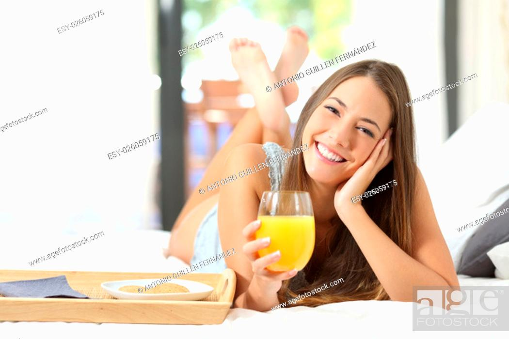 Stock Photo: Happy girl having breakfast with orange juice on the bed at home and looking at camera.