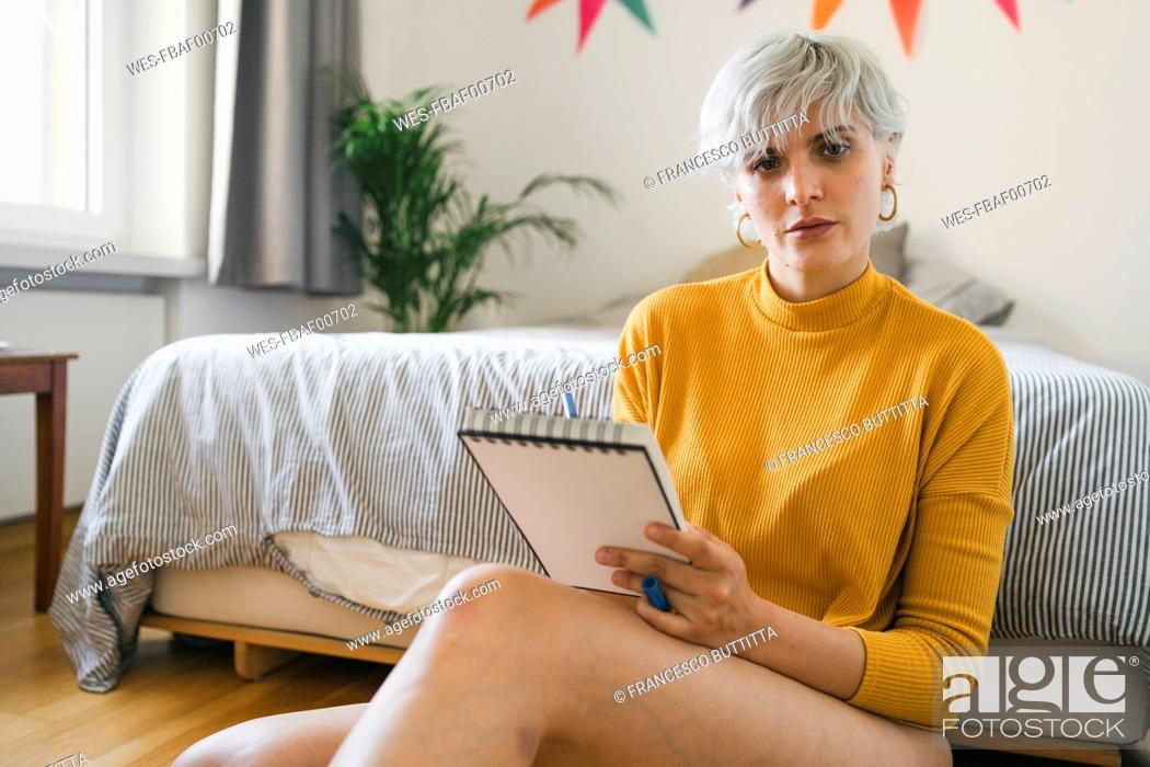 Stock Photo: Portrait of woman sitting next to bed at home with notepad.