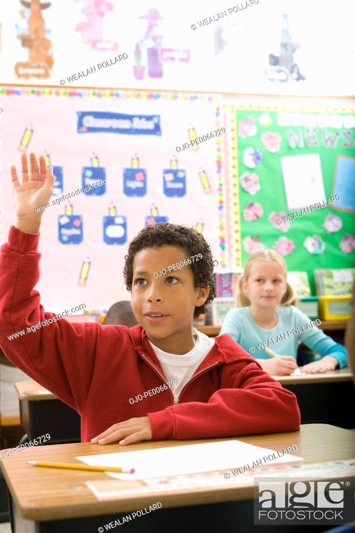 Stock Photo: Boy raising hand in classroom.