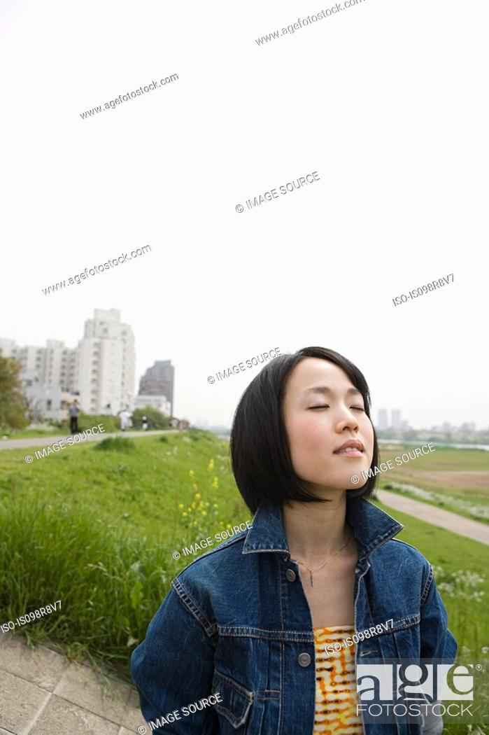 Stock Photo: Young woman outdoors with eyes closed.
