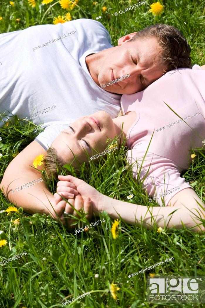 Stock Photo: Germany, Bavaria, Munich, Young couple lying in meadow, elevated view.