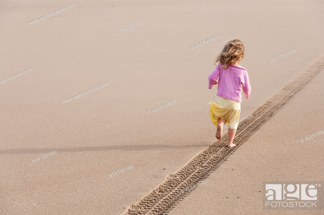 Stock Photo: Young girl, four years old, running along a tyre track on a sandy beach.