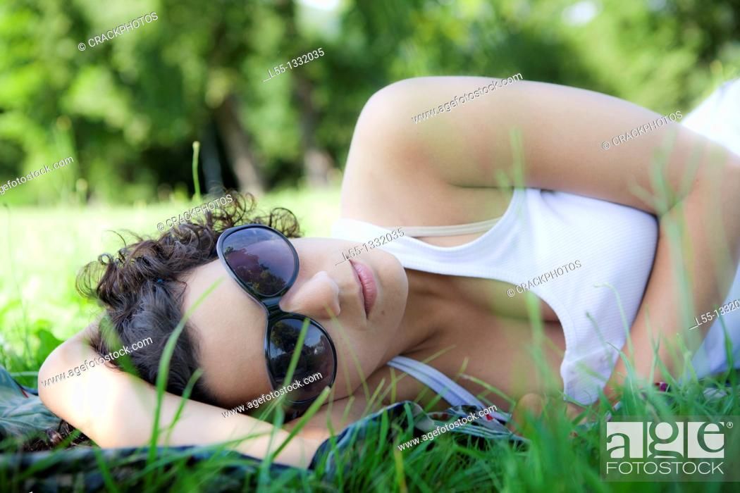Stock Photo: Woman lying down on grass.