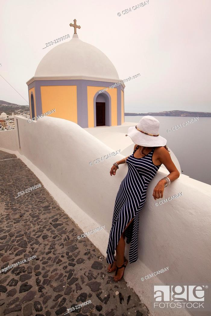 Stock Photo: Woman in front of a yellow domed church in Fira town, Santorini, Cyclades Islands, Greek Islands, Greece, Europe.