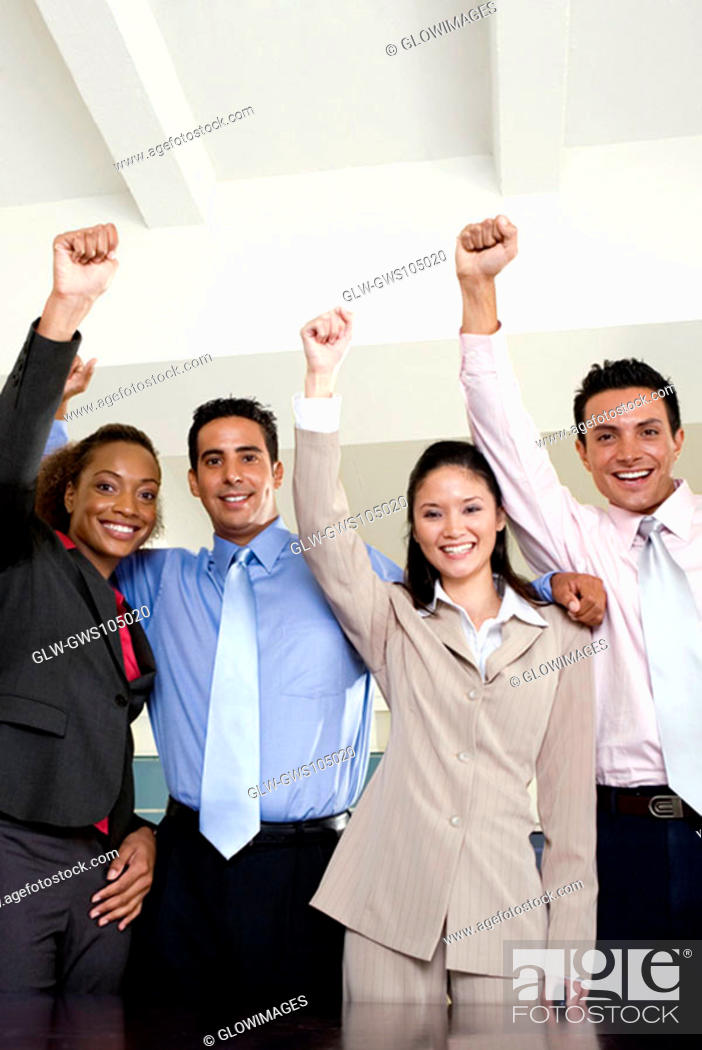 Stock Photo: Portrait of two businessmen and two businesswomen standing with their hands raised.