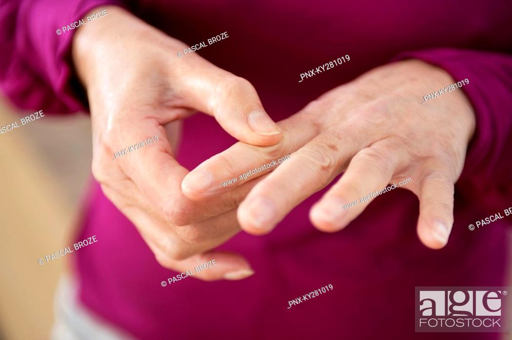 Stock Photo: Close-up of a woman suffering from finger pain.